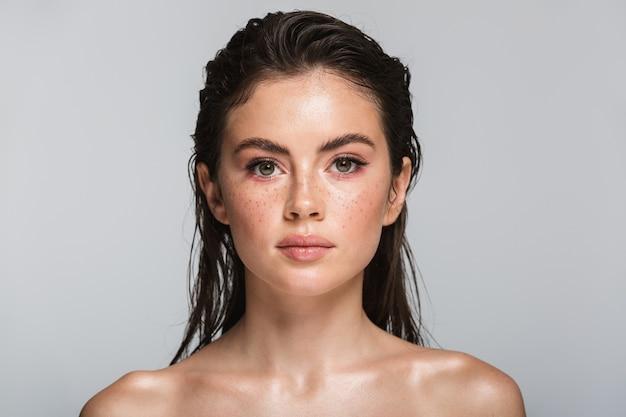Piękno portret atrakcyjnej młodej topless brunetki kobiety stojącej na białym tle