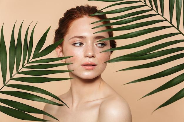 Piękno portret atrakcyjnej młodej topless rudej kobiety stojącej na białym tle, pozującej otoczonej tropikalnymi liśćmi