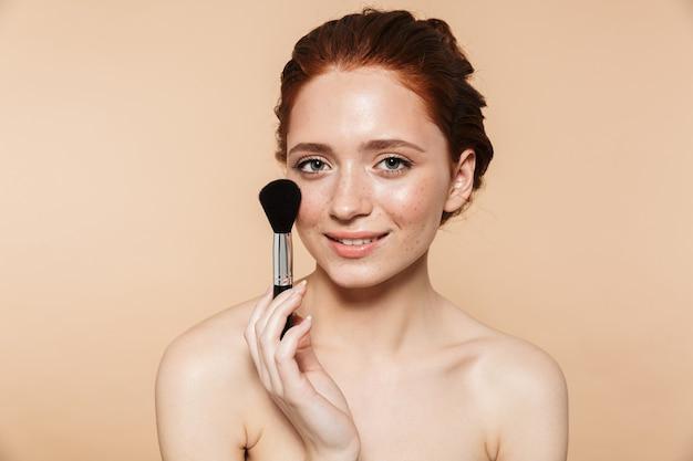 Piękno portret atrakcyjnej młodej topless rudej kobiety stojącej na białym tle, trzymającej pędzel do makijażu