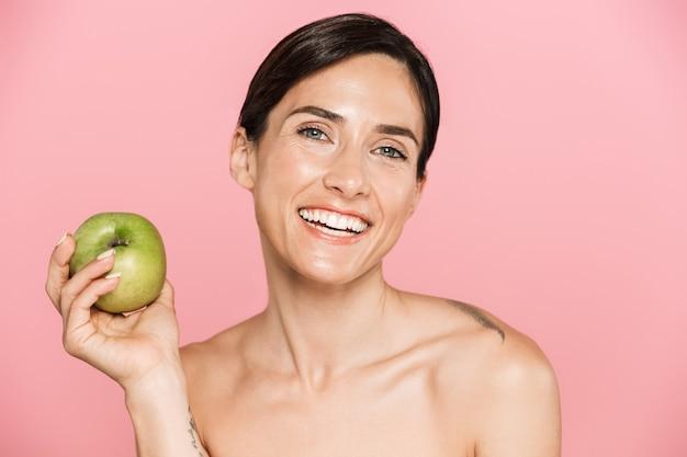 Piękno portret atrakcyjnej szczęśliwej młodej kobiety topless stojącej na białym tle, trzymającej zielone jabłko