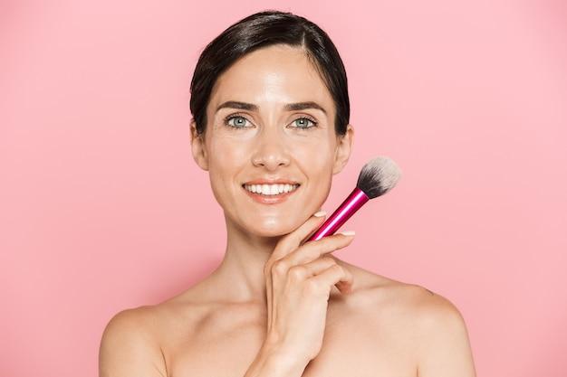 Piękno portret atrakcyjnej uśmiechniętej młodej kobiety topless stojącej na białym tle nad różową ścianą, trzymającej pędzel do makijażu