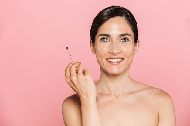 Piękno portret atrakcyjnej uśmiechniętej zdrowej brunetki topless odizolowanej nad różową ścianą, trzymającej strzykawkę