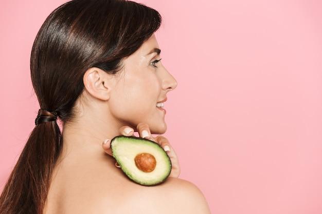 Piękno portret atrakcyjnej uśmiechniętej zdrowej topless brunetki na białym tle, pokazując pokrojone awokado