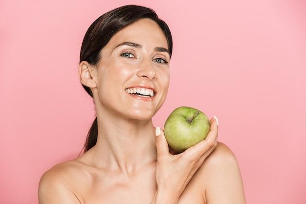Piękno portret atrakcyjnej uśmiechniętej zdrowej topless brunetki na białym tle, pokazując zielone jabłko