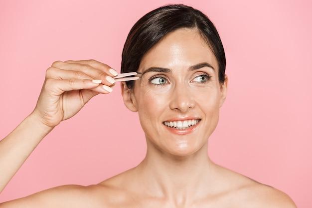 Piękno portret atrakcyjnej uśmiechniętej zdrowej topless brunetki na białym tle za pomocą pęsety