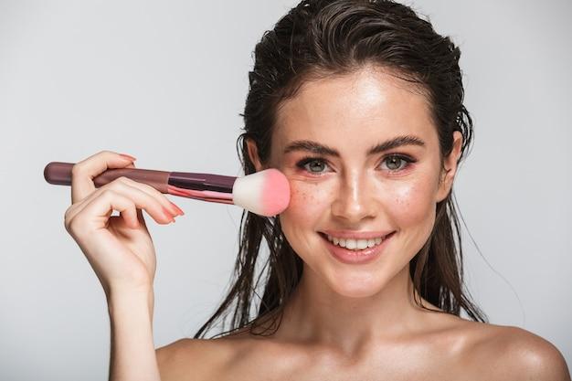 Piękno portret atrakcyjnej uśmiechniętej zmysłowej młodej kobiety z mokrą brunetką, długimi włosami stojącej na szarym tle, za pomocą pędzla do makijażu