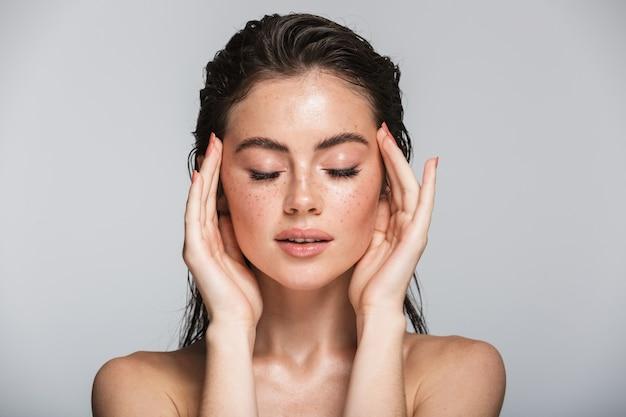 Piękno portret atrakcyjnej uśmiechniętej zmysłowej młodej kobiety z mokrymi brunetkami długimi włosami stojącej na szarym tle, dotykającej jej twarzy, pozującej