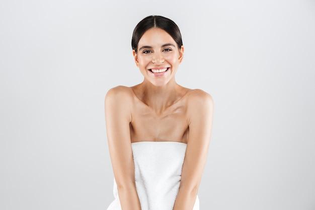 Piękno portret atrakcyjnej zdrowej kobiety stojącej na białym tle nad białą ścianą, pozowanie