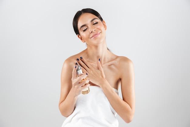 Piękno portret atrakcyjnej zdrowej kobiety stojącej na białym tle nad białą ścianą, stosując olejek do ciała