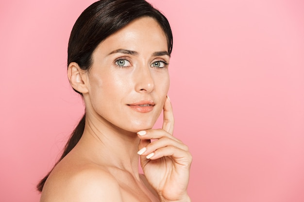 Piękno portret atrakcyjnej zmysłowej brunetki topless kobiety stojącej na białym tle, dotykającej jej twarzy