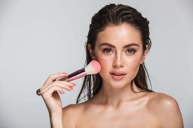 Piękno portret atrakcyjnej zmysłowej młodej kobiety z mokrą brunetką, długimi włosami stojącej na szarym tle, używając pędzla do makijażu