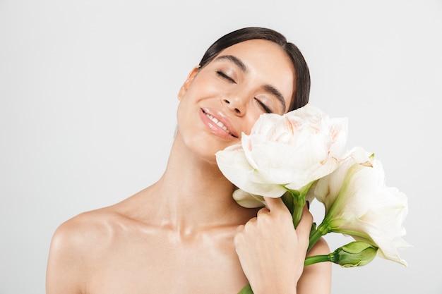 Piękno portret atrakcyjnej zmysłowej zdrowej kobiety stojącej na białym tle nad białą ścianą, pozowanie z kwiatem