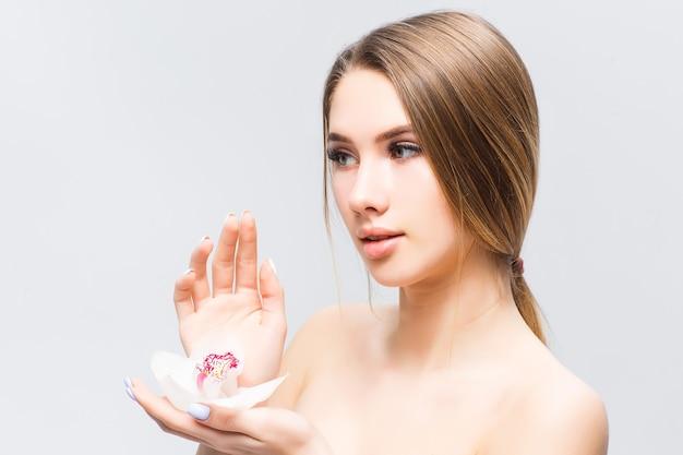 Piękno portret atrakcyjnej zmysłowej zdrowej kobiety stojącej na białym tle nad szarą ścianą, pozującej z kwiatem