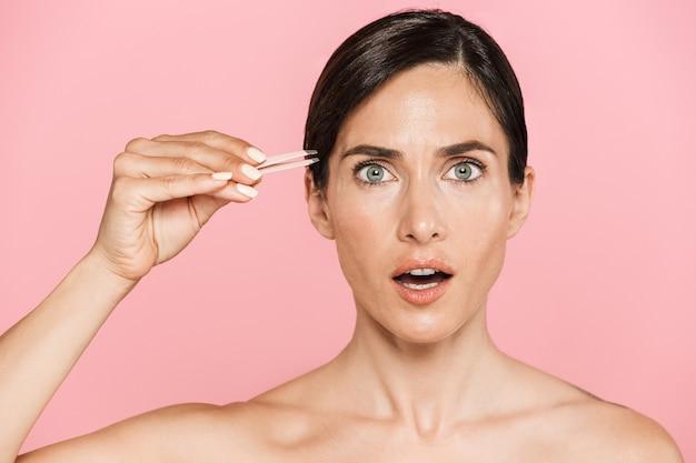 Piękno portret atrakcyjnej zszokowanej zdrowej topless brunetki na białym tle, za pomocą pęsety