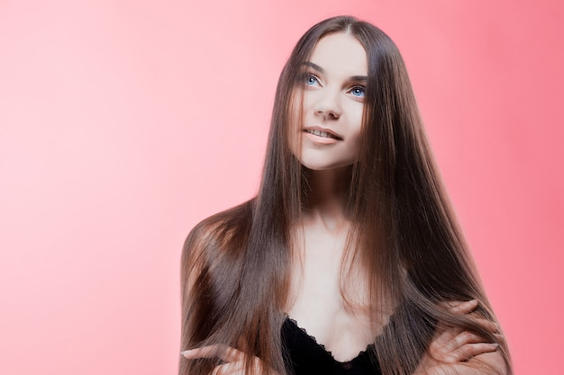 Piękno portret brunetka z doskonałymi włosami, na różowej ścianie. pielęgnacja włosów