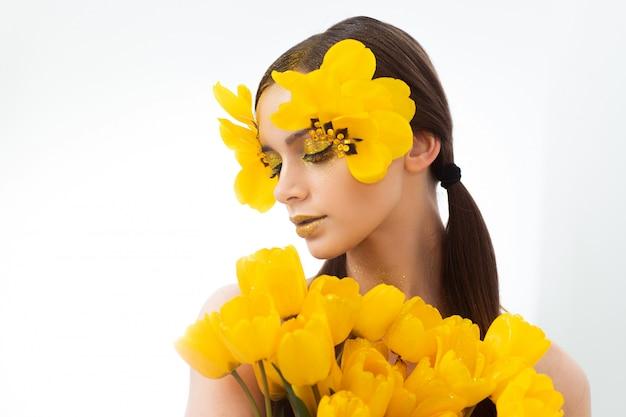 Piękno portret brunetki z przedłużonymi rzęsami na obrazku tulipana. na białym