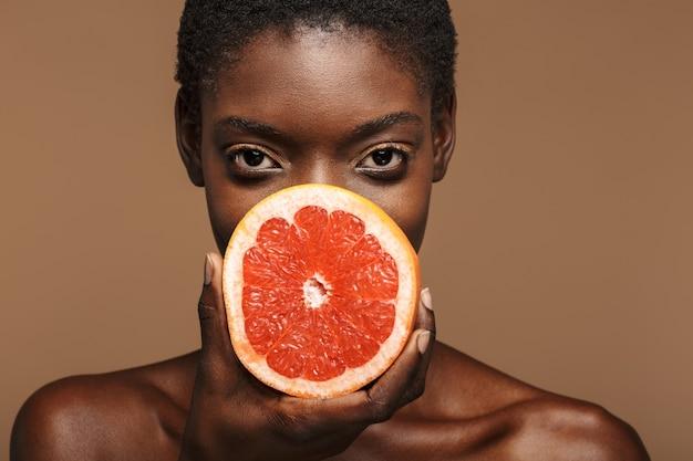 Piękno portret całkiem młodej półnagiej afrykańskiej kobiety trzymającej część grejpfruta odizolowaną na brązowo