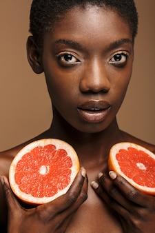 Piękno portret całkiem młodej półnagiej afrykańskiej kobiety trzymającej części grejpfruta izolowane na brązowym