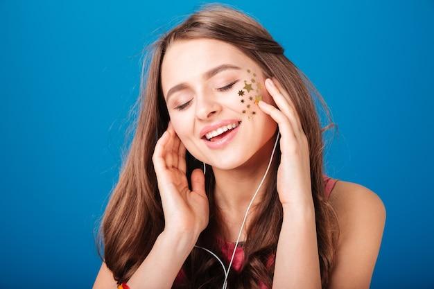 Piękno portret całkiem szczęśliwej młodej kobiety z dekoracją w kształcie gwiazdy na policzku na niebieskim tle
