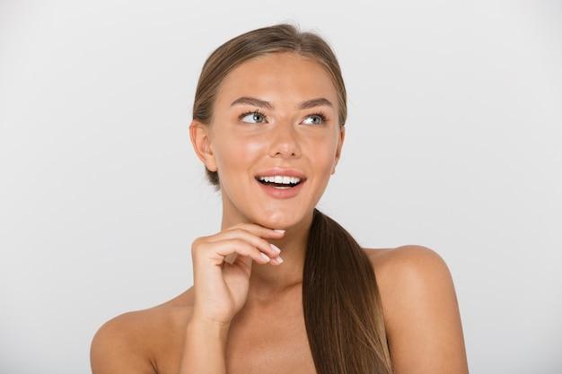 Piękno portret europejskiej kobiety bez koszuli z długimi brązowymi włosami, uśmiechając się i patrząc na bok, na białym tle