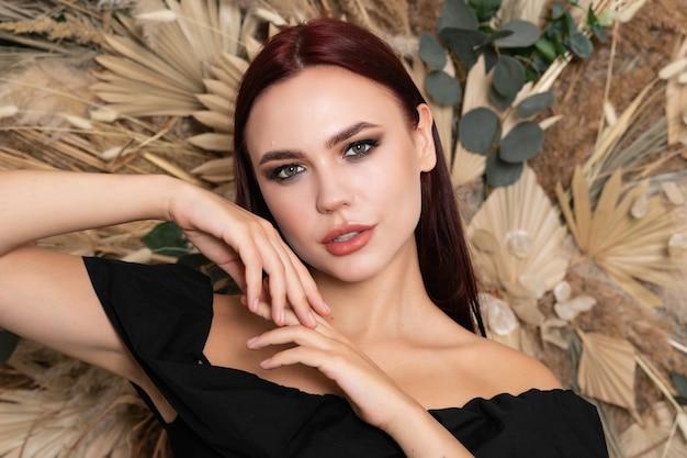 Piękno portret kobiecej twarzy z naturalną skórą. brunetka dziewczyna z bordowymi ustami na tle wiosennych kwiatów polnych suchych. otwarte ramiona