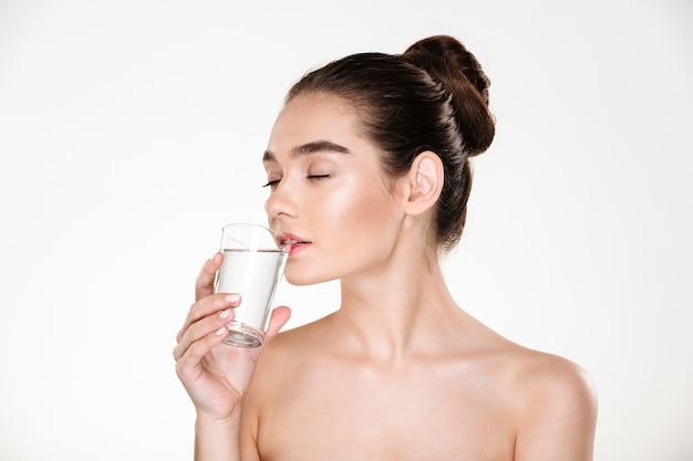 Piękno portret kobiety bardzo kobiece o miękkiej skórze, picie świeżej wody niegazowanej z przezroczystego szkła z zamkniętymi oczami