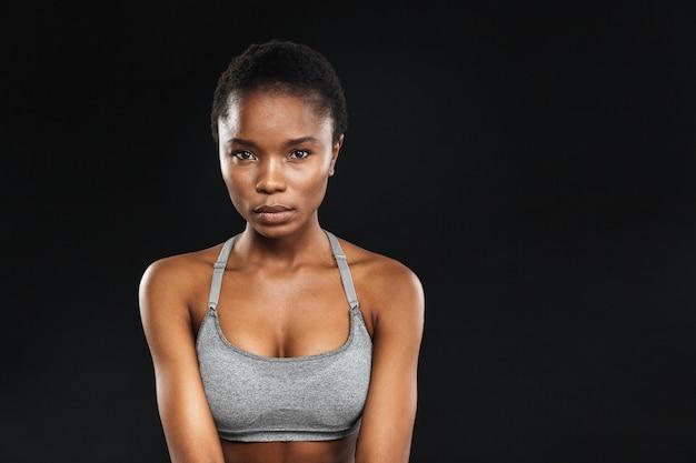 Piękno portret kobiety fitness z idealną skórą patrząc z przodu na białym tle na czarnej ścianie