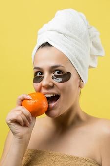Piękno portret kobiety w biały ręcznik na głowie ze złotą maską odżywczą na twarzy. pielęgnacja skóry, oczyszczanie eko organiczne kosmetyczne spa relaks koncepcja. dziewczyna stoi plecami trzymając pomarańczową mandarynek.