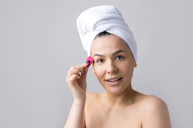 Piękno portret kobiety w białym ręczniku na głowie z gąbką do ciała w świetle różowego serca