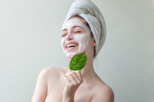 Piękno portret kobiety w ręcznik na głowie z białą odżywczą maską lub kremem na twarzy i zielonym liściem w dłoni, na białym tle.