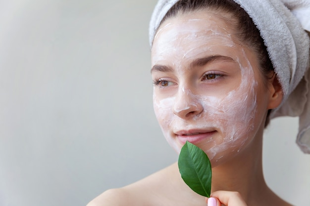 Piękno portret kobiety w ręczniku na głowie z białą odżywczą maską lub kremem na twarzy i zielonym liściem w dłoni