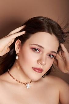 Piękno portret kobiety z biżuterią, kolczykami w uszach i naszyjnikiem na szyi