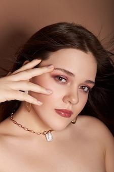 Piękno portret kobiety z biżuterią, kolczykami w uszach i naszyjnikiem na szyi.