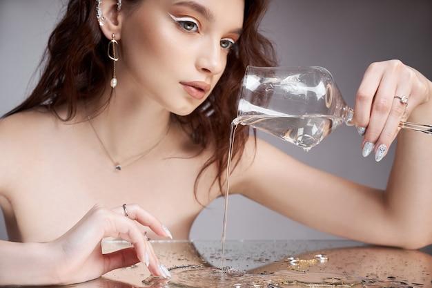 Piękno portret kobiety z kieliszkiem w ręku. pierścienie są na stoliku z lustrem. kosmetyki naturalne