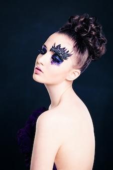 Piękno portret kobiety z kreatywnym makijażem i fryzurą na czarnym tle