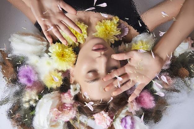 Piękno portret kobiety z kwiatami i płatkami za szkłem w kroplach deszczu. kosmetyki do twarzy, nawilżające skórę. brak ostrości, selektywna ostrość i szum