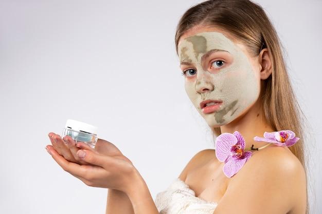 Piękno portret kobiety z maską na twarz, gałązką orchidei i serum przeciwstarzeniowym w jej rękach białą ścianą