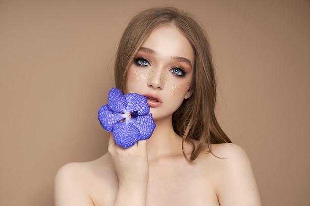Piękno portret kobiety z niebieską orchideą vanda w ręku.