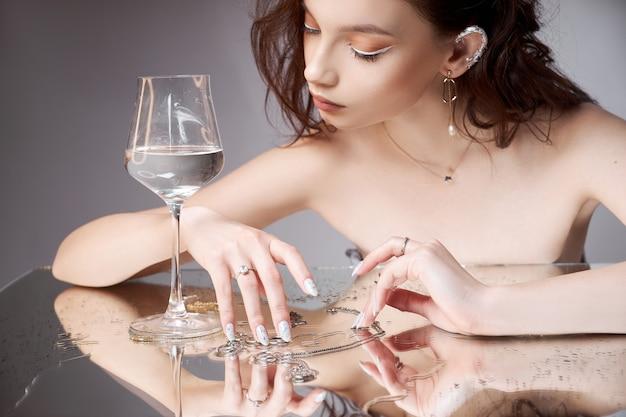 Piękno portret kobiety ze szklanką w ręku. pierścienie są na stoliku lustrzanym. kosmetyki naturalne