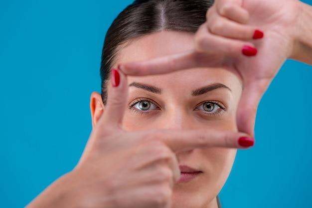 Piękno portret młodej atrakcyjnej kobiety brunetka o doskonałej skórze pozowanie i pokazując ramkę palcami. kryty, na niebiesko