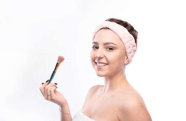 Piękno portret młodej atrakcyjnej pół naga kobieta z pędzlem i doskonałej skóry, pozowanie i odwracając na białym tle nad białym.