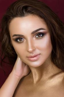 Piękno portret młodej kobiety ładny makijaż moda. opalona skóra i złote dymne oczy.