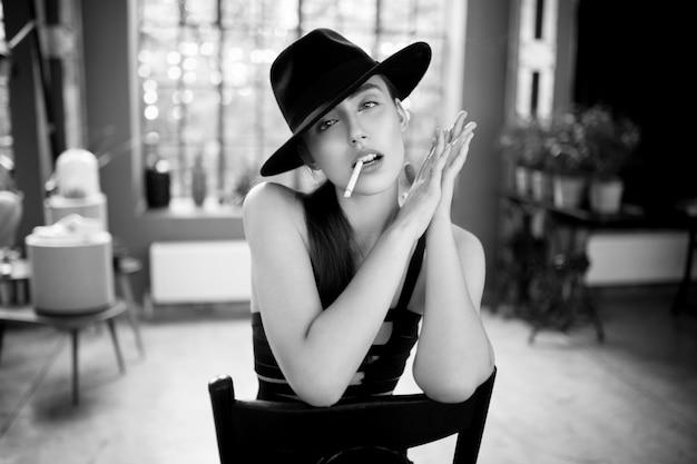 Piękno portret młodej kobiety palenia w czarnym kapeluszu