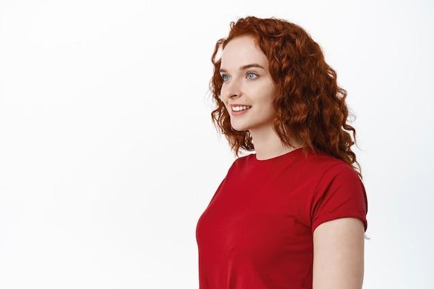 Piękno. portret młodej kobiety z rudymi kręconymi włosami i bladą gładką skórą, patrzącą w lewo na pustą przestrzeń, uśmiechniętą szczęśliwą, białą ścianą