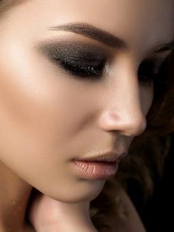 Piękno portret młodej kobiety z złoty makijaż. idealny makijaż skóry i mody ze złotymi akcentami.