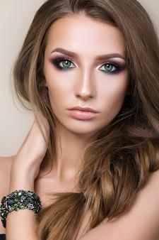 Piękno portret młodej ładnej dziewczyny z zielonymi oczami na sobie zieloną bransoletkę i dotykając jej włosów