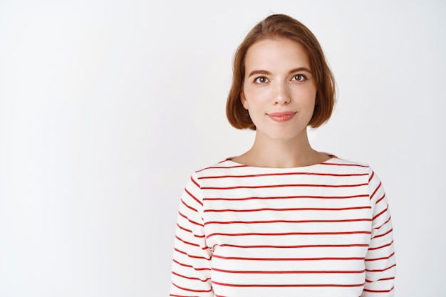 Piękno. portret młodej, pewnej siebie kobiety z naturalną jasną skórą twarzy, uśmiecha się czule, stojąc w pasiastej bluzce na białej ścianie