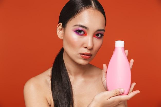 Piękno portret młodej topless azjatyckiej kobiety z brunetką w jasnym makijażu, stojącej odizolowanej na czerwono, pokazującej pustą butelkę po szamponie