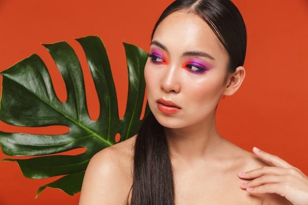 Piękno portret młodej topless azjatyckiej kobiety z brunetką w jasnym makijażu, stojącej odizolowanej na czerwono, pozującej z tropikalnym liściem