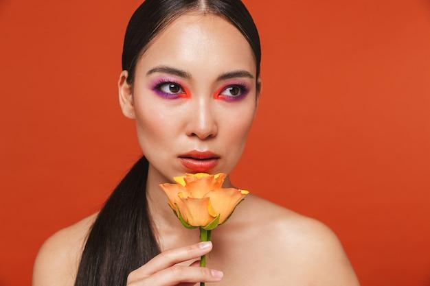 Piękno portret młodej topless azjatyckiej kobiety z brunetką w jasnym makijażu, stojącej odizolowanej na czerwono, pozującej z żółtą różą